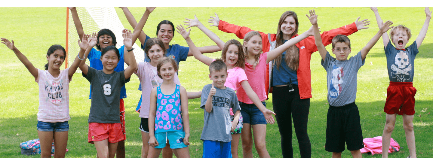 Group of campers cheering with their hands in the air