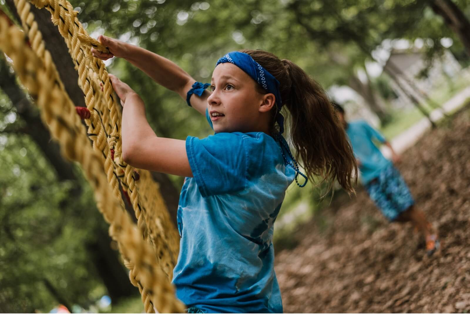Camper climbing on a Ninja Warrior course